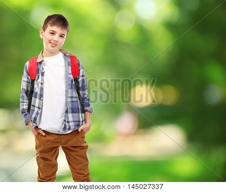 Cute boy with backpack on blurred green background. School concept.