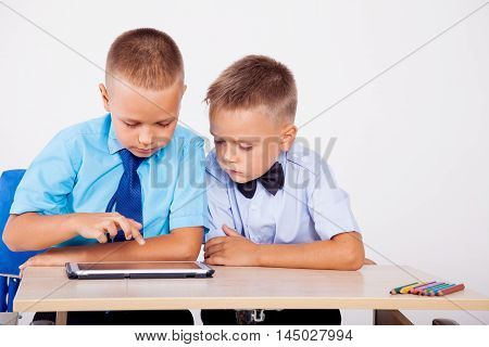 two boys sit at a desk and looking at Tablet
