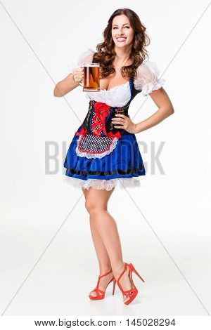 Beautiful young brunette girl in dirndl drinks out of oktoberfest beer stein. on white background. full-length