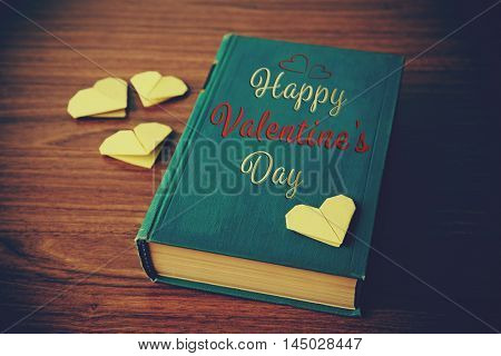Book and origami hearts on wooden background. Text happy valentines day.
