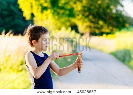 Little Boy Playing With Slingshot