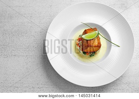 Plate of delicious meat with rice and lime on white wooden background