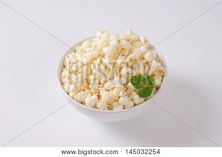 bowl of fresh popcorn on off-white background with shadows