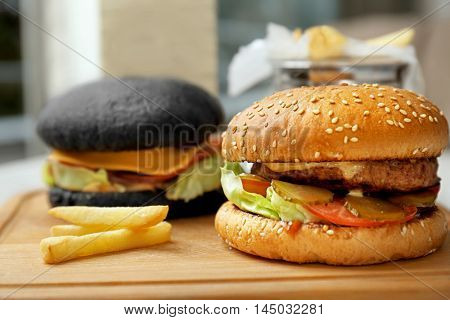 Two different burgers on wooden cutting board