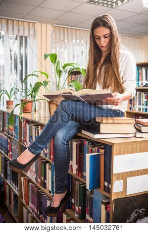 Happy lady reading books in library while sitting on bookshelf. Long-haired lady looking into a book.
