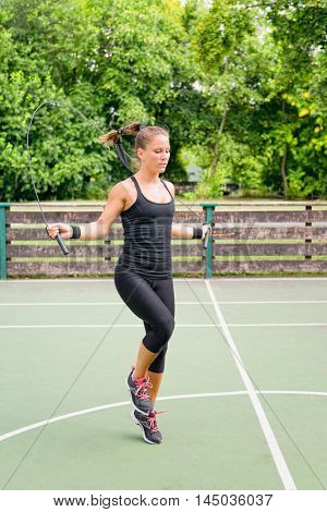 Young female athlete jumping rope, toned image