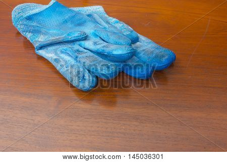 blue working gloves handle on wooden table