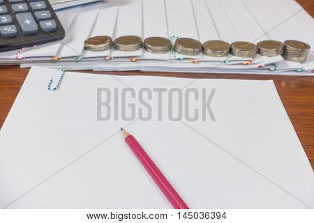 pencil reports arranged and document place with paperclip have calculator and Coin on wooden floor.