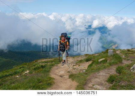 Backpacker climbs to the top of above the clouds. The difficult Trekking in Carpathian Mountains
