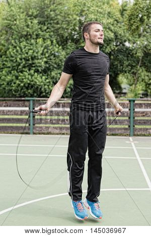 Male athlete jumping rope outdoors, toned image