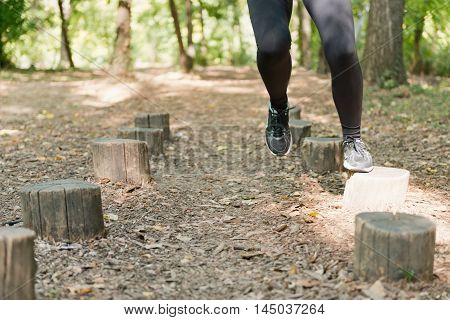 Running across fitness trail stumps, toned image