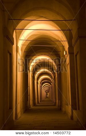 The ancient portico (arcade) of San Luca basilica in Bologna, Italy. Illuminated during the night.