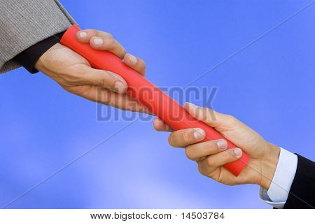 One businessman passing a red baton to another businessman. Symbol of teamwork, helping and partnership