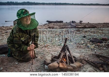 Girl hiker smiling and looking to camera around campfire on river shore at evening.