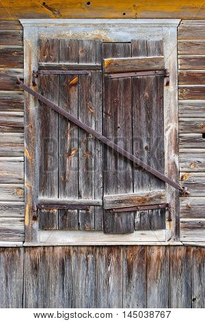 Closed window in a wooden house in the countryside