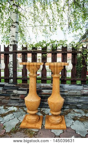Two terracotta flower stands at the garden. Gardening theme. Decorative objects. Vertical composition.