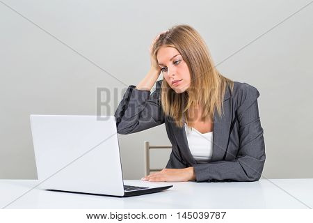 Portrait of very despair businesswoman looking at her laptop and sitting at the table.