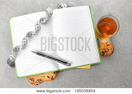 Notepad, measuring tape, juice and cookie on color background