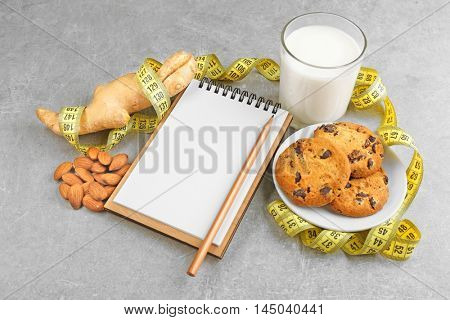 Notepad, milk and cookie on color background