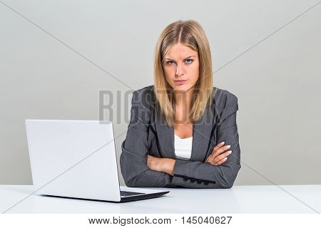 Portrait of very angry businesswoman with laptop sitting at the table.