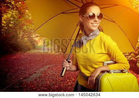 Pretty woman with umbrella in autumn day