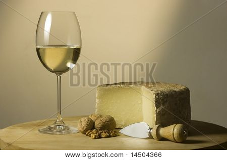 Cutting board with genuine Italian food. White wine glass, ripe hard cheese from ewe's milk and walnuts. Warm ray of light in the background.