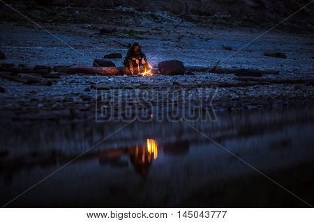Shot of a hiker at the dawn sitting near the camping fire. Concept of loneliness, choice, silence.High ISO, grainy image.