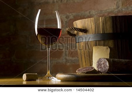 Cutting board with genuine Italian food in a rural kitchen. Red wine glass, ripe hard cheese from ewe's milk and sausage. Warm ray of light in the background.