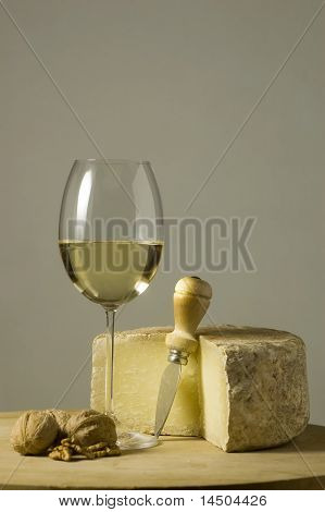 Cutting board with genuine Italian food. White wine glass, ripe hard cheese from ewe's milk and walnuts. Space for text