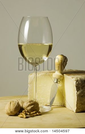 Cutting board with genuine Italian food. White wine glass and ripe hard cheese.