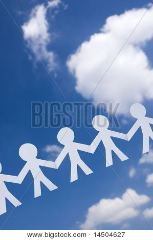 Paper man chain on blue sky with white clouds. Symbol of unity, brotherhood and teamwork