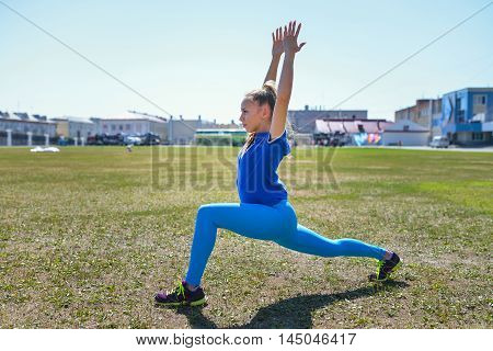Young slim woman makes Syrya Namaskara yoga pose.