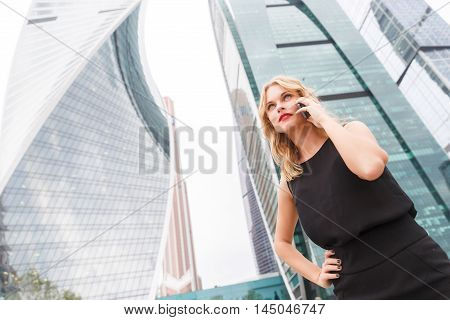 model in black dress with phone outdoor near building