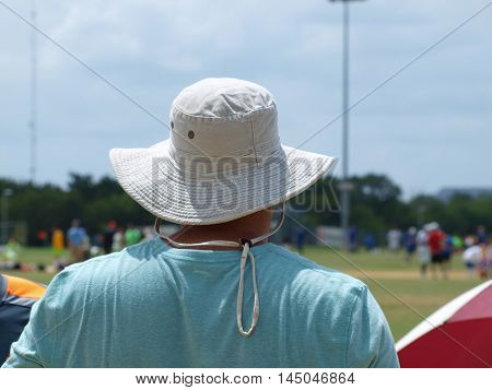 Soccer Spectator in favorite sports hat.watching several games.