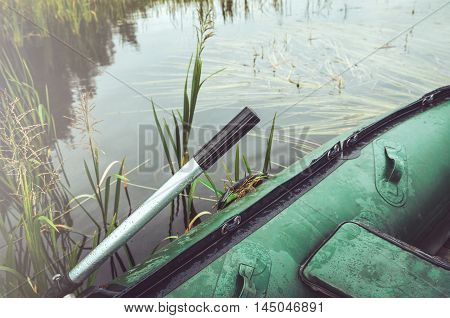 Concept fishing hiking. Green inflatable boat with silver paddle in a lake outdoor weekend on nature. Camping Holiday vacation. The Republic of Karelia Ladoga Lake Russia. Text copy space