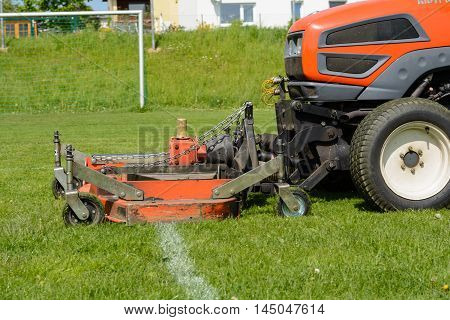 Lawn on football pitch is cut with lawn tractor