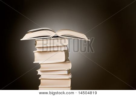 Open book on a high stack of hardcover ones against dark background. Space for text