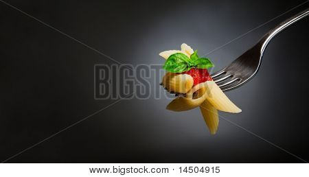 Pasta de macarrones con tomate y albahaca en horquilla. Buena comida italiana. Espacio para texto. Estudio profesional