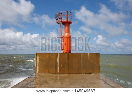 lighthouse at the end of pier with blue sky in background