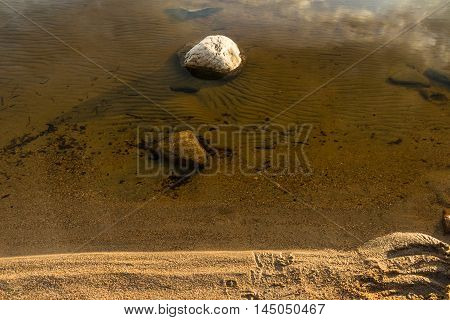 Stone in the clear water on the sandy shore of the lake