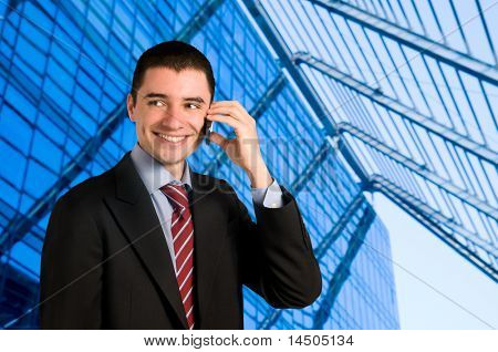 Portrait of young confident businessman talking on mobile phone outside the office