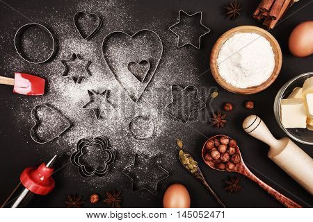 Food ingredients and kitchen utensils for cooking gingerbread or cookies on black background.