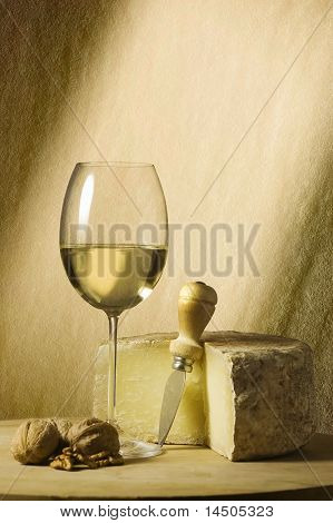 Cutting board with genuine Italian food. White wine glass, ripe hard cheese from ewe's milk and walnuts. Beam of light and space for text
