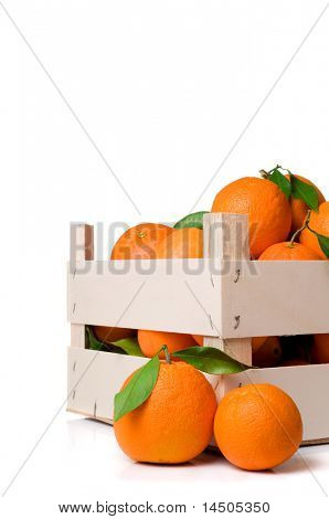 Fresh and ripe orange fruits with leaves in a wooden crate isolated on white background
