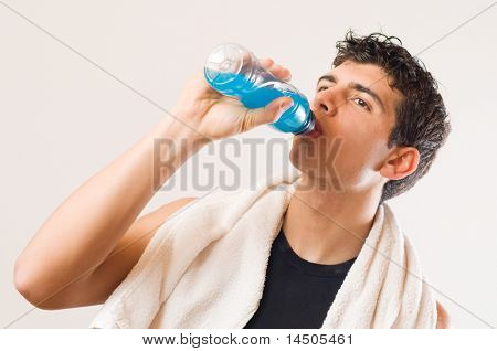 Young athletic man drinking energy drink after his exercising at gym