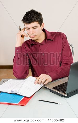 Young busy man studying and working on his laptop with note pad.