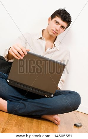 Young man working on his laptop with casual clothing and mobile phone