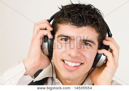 Portrait of young smiling man listening loud music in headphones