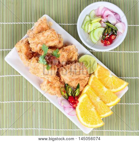 Fried tofu nuggets with minced shrimp and pork on green background.
