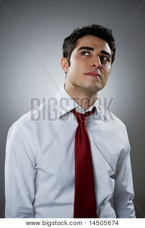 Young businessman looking up in a thoughtful expression